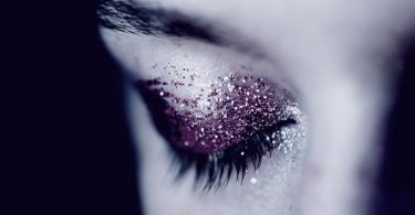 Close up beauty portrait of young woman with glittering makeup